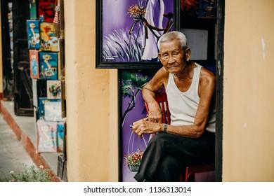 Hoi An, Vietnam / Vietnam - July 27 2013: Old Vietnamese man sitting outside his house