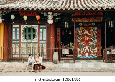 Hoi An, Vietnam / Vietnam - July 27 2013: Young vietnamese boy and old man sitting in front of beautiful traditional building in Vietnam