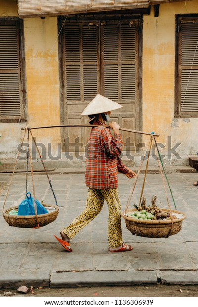 Hoi An, Vietnam / Vietnam - July 27 2013: Local Vietnamese woman selling her products at the street
