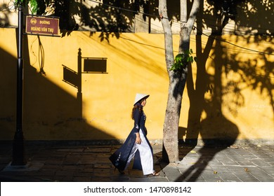 Hoi An, Vietnam - June 2019: Vietnamese woman walking and dropping shadow on yellow wall in old town district