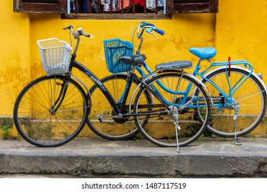 Hoi An, Vietnam - March 12, 2019:  Bicycles parked against a bright yellow wall in the old town of Hoi An, Vietnam.