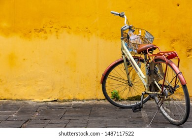 Hoi An, Vietnam - March 12, 2019:  A bicycle parked up against a bright yellow wall in the old town of Hoi An, Vietnam.