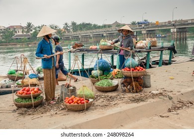 Hoi An, Vietnam - March 14, 2014: Women in conical hat and man unloading boat with goods for selling on fresh market on 14 March 2014, Hoi An, Vietnam.