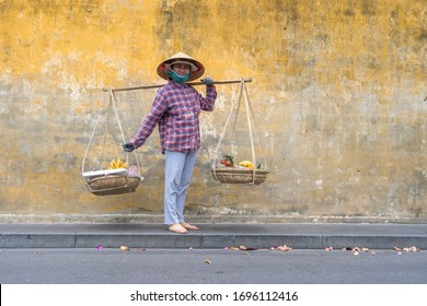 Hoi An, Vietnam - march 16, 2020 : Vietnamese woman in a straw hat with a basket of fruits on a street market in the old city against the background of the old yellow wall in Hoi An, Vietnam