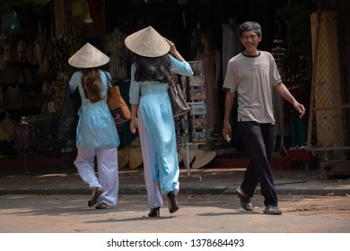 HOI AN, VIETNAM - MARCH 17, 2019: Young Vietnamese man smiling at two women wearing traditional Vietnamese robes and hats.