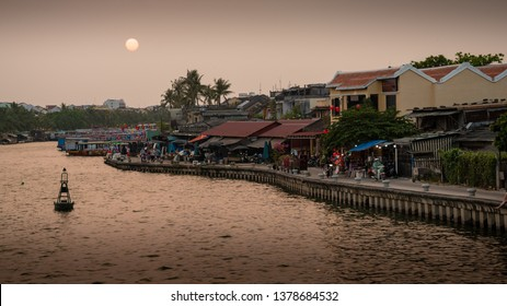 HOI AN, VIETNAM - MARCH 17, 2019: People going for a stroll at the shore of the Thu Bon river in the evening.