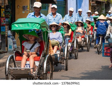HOI AN, VIETNAM - MARCH 21, 2019: Traditional Rickshaws (Cyclo) carrying tourists in the streets of Hoi An.