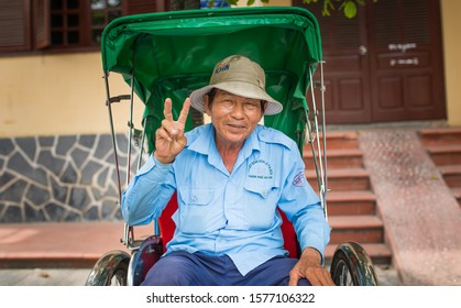 Hoi An, Vietnam. May 05, 2017. An elderly smiling Vietnamese rickshaw driver. A man is dressed in a blue corporate uniform. On the head is a hat with wide brim. Man shows a victory sign with his hand.