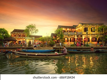 Hoi An, Vietnam - May 8, 2017:  Street view with traditional boats on a background of ancient town in Hoi An, Vietnam.