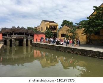 HOI AN, VIETNAM - OCTOBER 2017: Tourists by the Bridge Pagoda or Japanese Bridge built in the 17th century, one of the prominent landmarks in the city