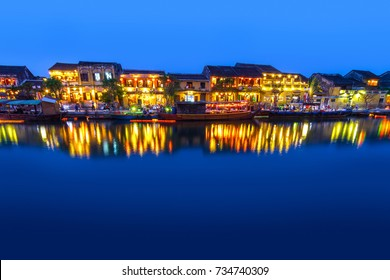 Hoi An, Vietnam riverside cafes, shops, and boats just after sunset.