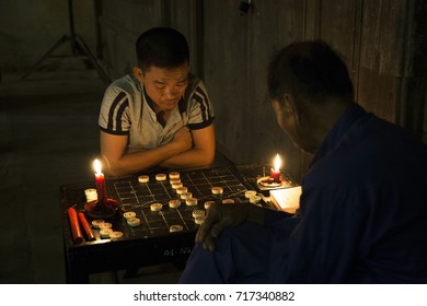 Hoi An, Vietnam - Sep 5, 2017: Two men playing Chinese chess on the sidewalk at full moon night in Hoi An ancient town, Vietnam.