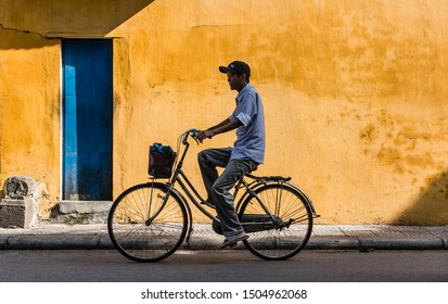 Hoi An, Vietnam, September 2019: yellow wall house in  Hoi An, Vietnam with a silhouette of a person on a bicycle passing by
