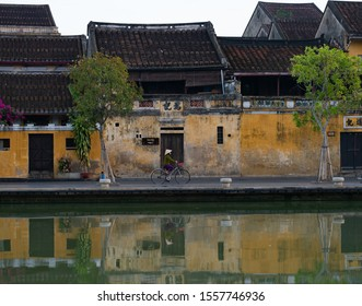 Hoi An, Vietnam - September 22, 2018: Woman wearing a non la or straw hat while riding a bicycle along the riverfront of the old city in Hoi An, Vietnam.