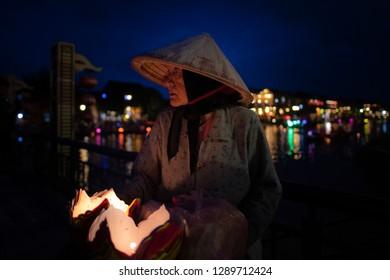 Hoi An, Vietnam-December 12, 2018: A local Vietnamese elder is selling floating paper baskets in heritage site, Hoi An, Vietnam.