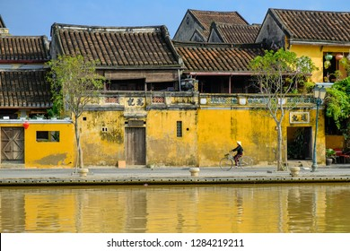 Hoi An/Vietnam, 12/11/2017: Local Vietnamese woman with rice hat on a bicycle passing in front of traditional houses with ornamental yellow walls and tiled roofs next to the river in Hoi An, Vietnam.