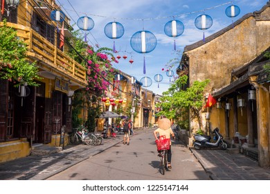 Hoi An/Vietnam - July, 2018: Vietnamese local woman is on the way home from the morning market, through the street of Hoi An ancient town.