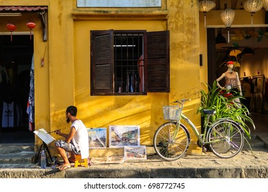 HOI AN,Vietnam-August 12,2017 : Street activity for tourist ,people sit to draw  at street side on vintage old house Unesco world heritage Vietnam