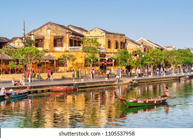 Hoi An (Hoian), Vietnam - April 11, 2018: Beautiful view of traditional yellow building in Hoi An Ancient Town. Tourists walking along embankment of the Thu Bon River. Boatman on the river.