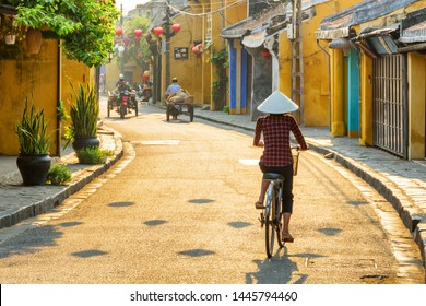Hoi An (Hoian), Vietnam - April 12, 2018: Vietnamese woman in traditional bamboo hat bicycling along Hoi An Ancient Town. Awesome view of old street decorated with colorful silk lanterns at sunrise.