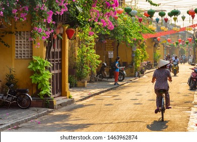 Hoi An (Hoian), Vietnam - April 12, 2018: Wonderful view of old street decorated with colorful silk lanterns at sunrise. Vietnamese woman in traditional bamboo hat bicycling along Hoi An Ancient Town.