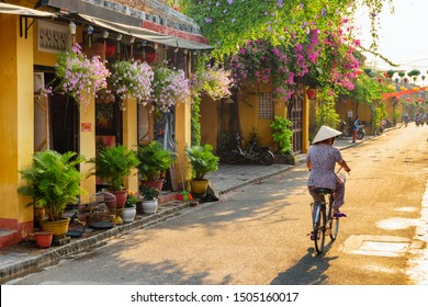 Hoi An (Hoian), Vietnam - April 12, 2018: Amazing view of old street decorated with colorful silk lanterns at sunrise. Vietnamese woman in traditional bamboo hat bicycling along Hoi An Ancient Town.