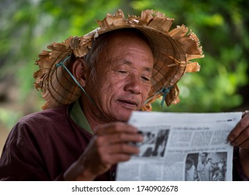 HOI AN - MAR 10, 2018: An old man with an Asian conical hat reading newspaper outdoor under a street on the street in Hoi An, Vietnam on 10 March 2018