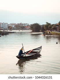 Hoi An at sunset in Vietnam, old lady takes her boat along the river