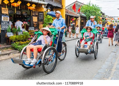 HOIAN,VIETNAM-JULY 21,2018: Tourists ride on traditional bicycle.(cyclo)  to see the ancient yellow house.Here is a UNESCO World Heritage Site.