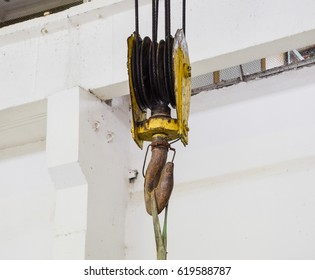 Hoist with winch and hook. A tool for moving goods in a production room. Mechanization of labor.