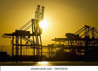 hoisting crane in a harbor, lifting cargo onto a container ship