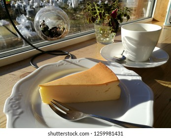 Hokkaido Cheesecake and Cup of black coffee on wooden bar in coffee shop with morning sunshine. Japan.