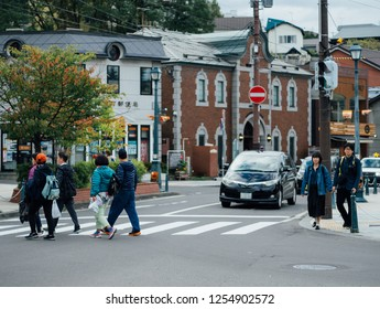 HOKKAIDO, JAPAN : September 22, 2018 - Group of tourist walking on crosswalk sign at Otaru Music Box Museum in Hokkaido, Japan.