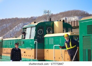 HOKKAIDO, JAPAN-1 FEB. 2013: Train Conductor in Hokkaido, Japan on Feb, 1, 2013, a snow day. Unidentified Japanese train conductor observes passenger before giving a sign to move the train.