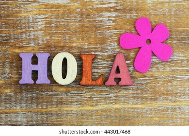 Hola (which means hello in Spanish) written with colorful wooden letters and pink flower