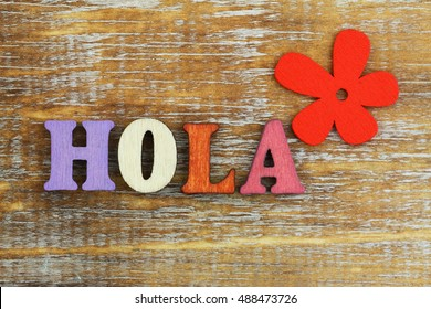Hola (which means hello in Spanish) written with colorful wooden letters and red flower