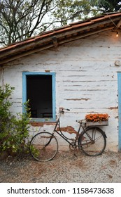 HOLAMBRA, SAO PAULO, BRAZIL - 20-SEPTEMBER, 2014: Typical and Rustic house exposed  on 33ª Expoflora Flower Fair in Holambra and a bike with flowers outside