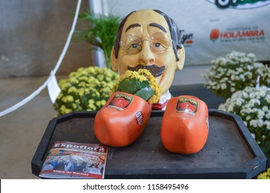 HOLAMBRA, SAO PAULO, BRAZIL - 20-SEPTEMBER, 2014: Dutch man statue and wooden clog next to leaflet on 33ª Expoflora Flower Fair in Holambra