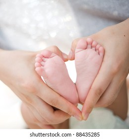 hold baby's foot as love heart shape