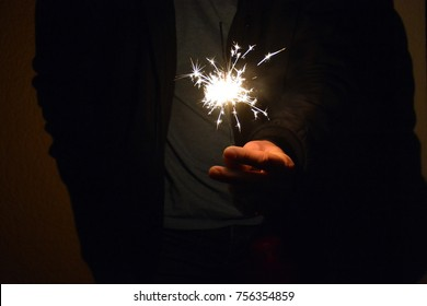 Hold a burning sparkler in your hand during the night