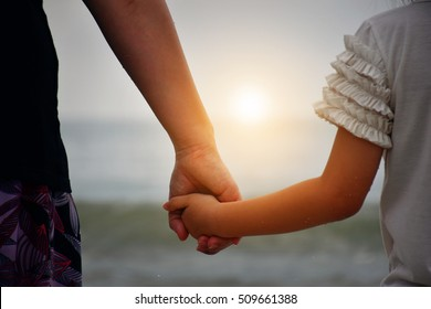 Hold my hand.Mother and daughter holding hands for watching the sunset together.Love concept