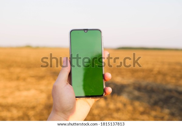Mantenga el teléfono con pantalla verde. Marcando campo. Tecnología moderna. Conexión 5G. Producción agrícola. Copiar espacio