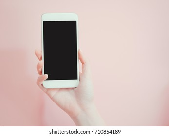 hold and show smart phone by asian woman beauty right hand with pink pastel background