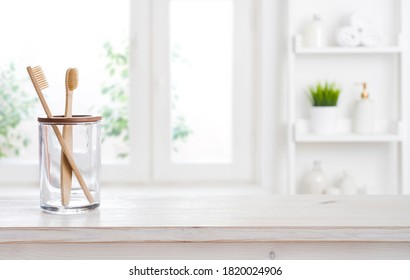 Holder with bamboo toothbrushes on wooden table against defocused background