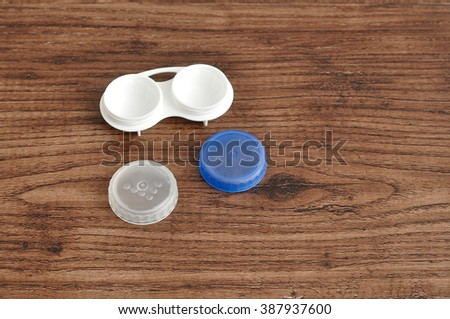 A holder for contact lenses isolated on a wooden background