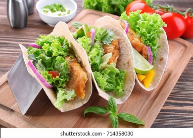 Holder with delicious fish tacos on wooden table