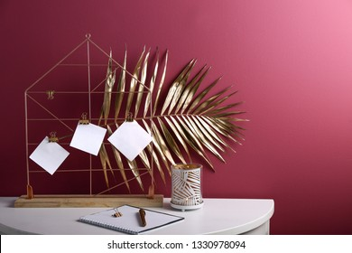 Holder with golden tropical leaf and stationery on white table near color wall