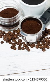holder with ground coffee and cup of coffee on white background, vertical top view
