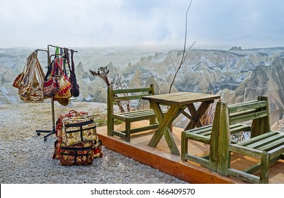 The holder with many colorful bags next to the tables of outdoor cafe in mountains of Cappadocia, Turkey.
