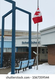 HOLDFAST, SASKATCHEWAN/CANADA-April 12 2018: Schell School flies the Canadian flag at half mast above a hockey stick tribute to the Humboldt Broncos killed in a tragic bus accident on April 6. 2018.